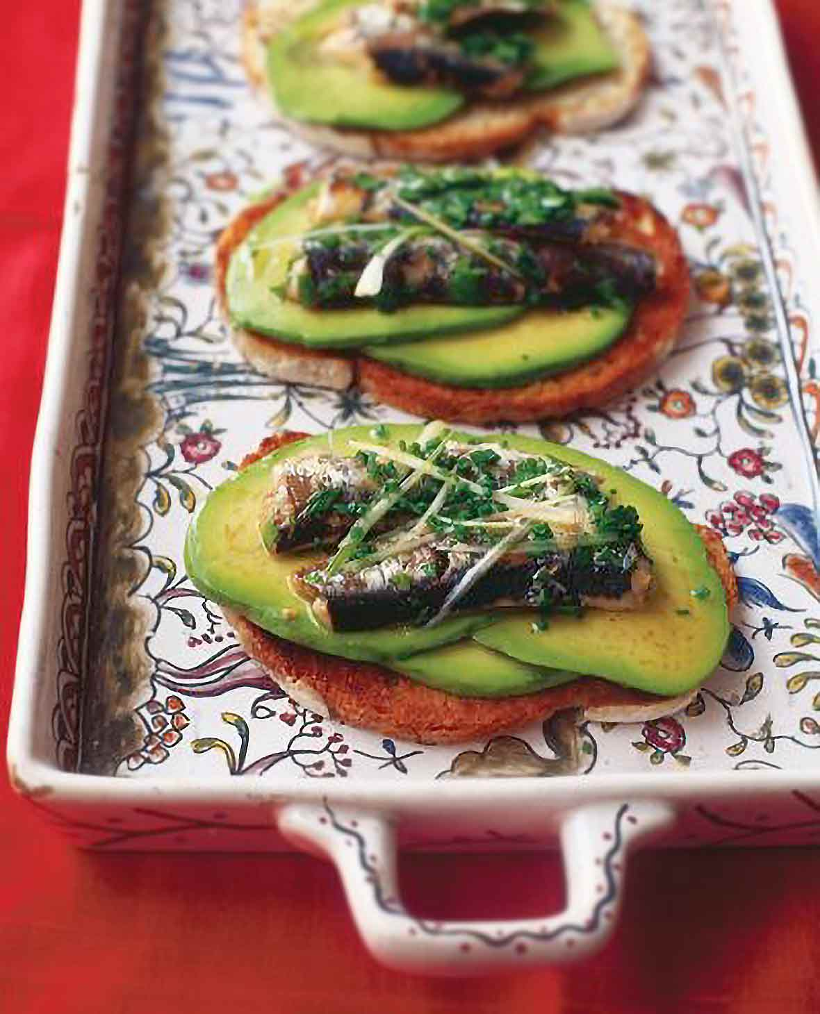 A decorative tray with avocado-sardine toasts--crispy slices of bread topped with avocado, marinated sardines, and scallion and chives