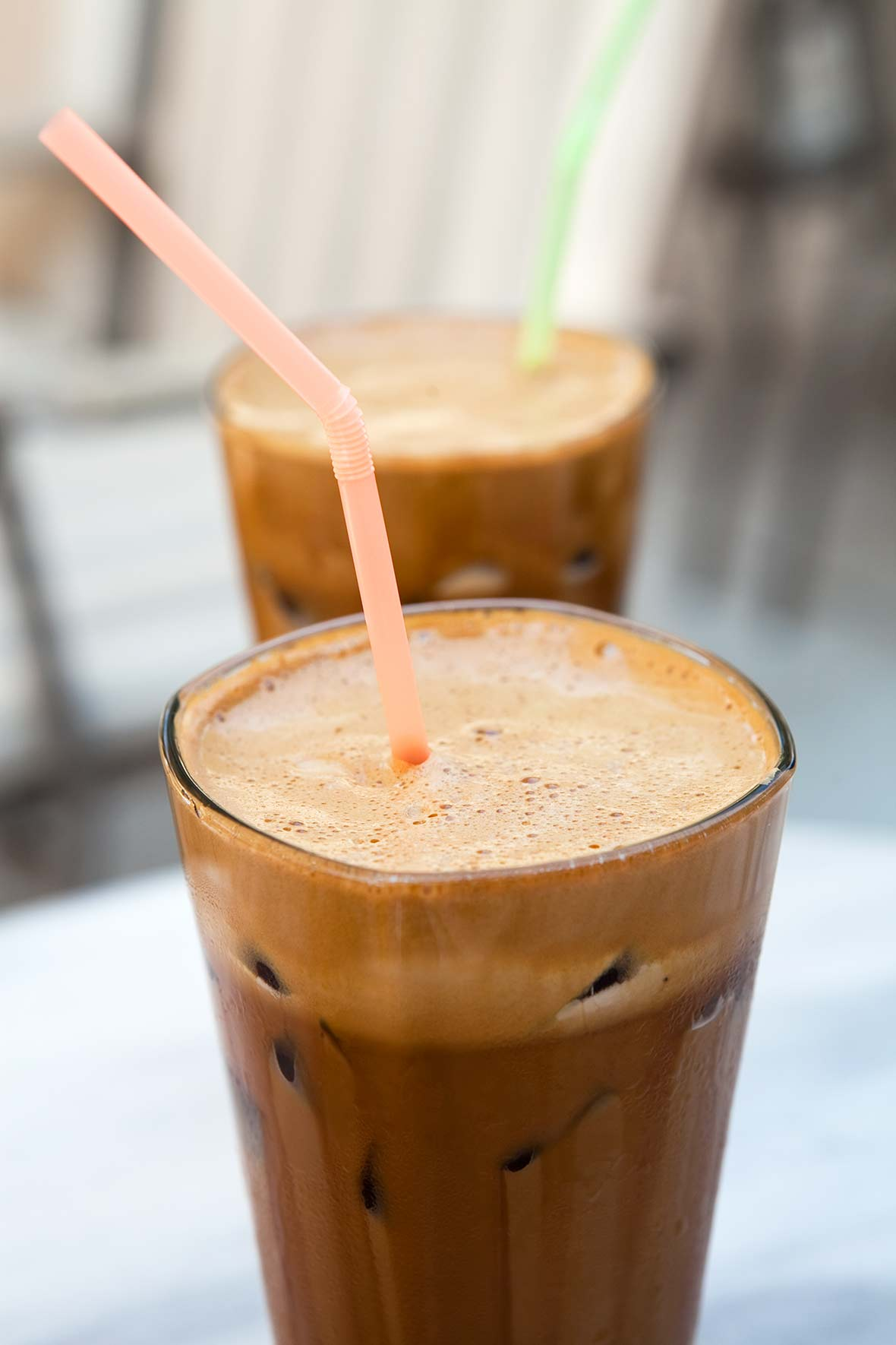 Two tall glasses filled with Greek-style frappe, with colorful straws standing up in them.