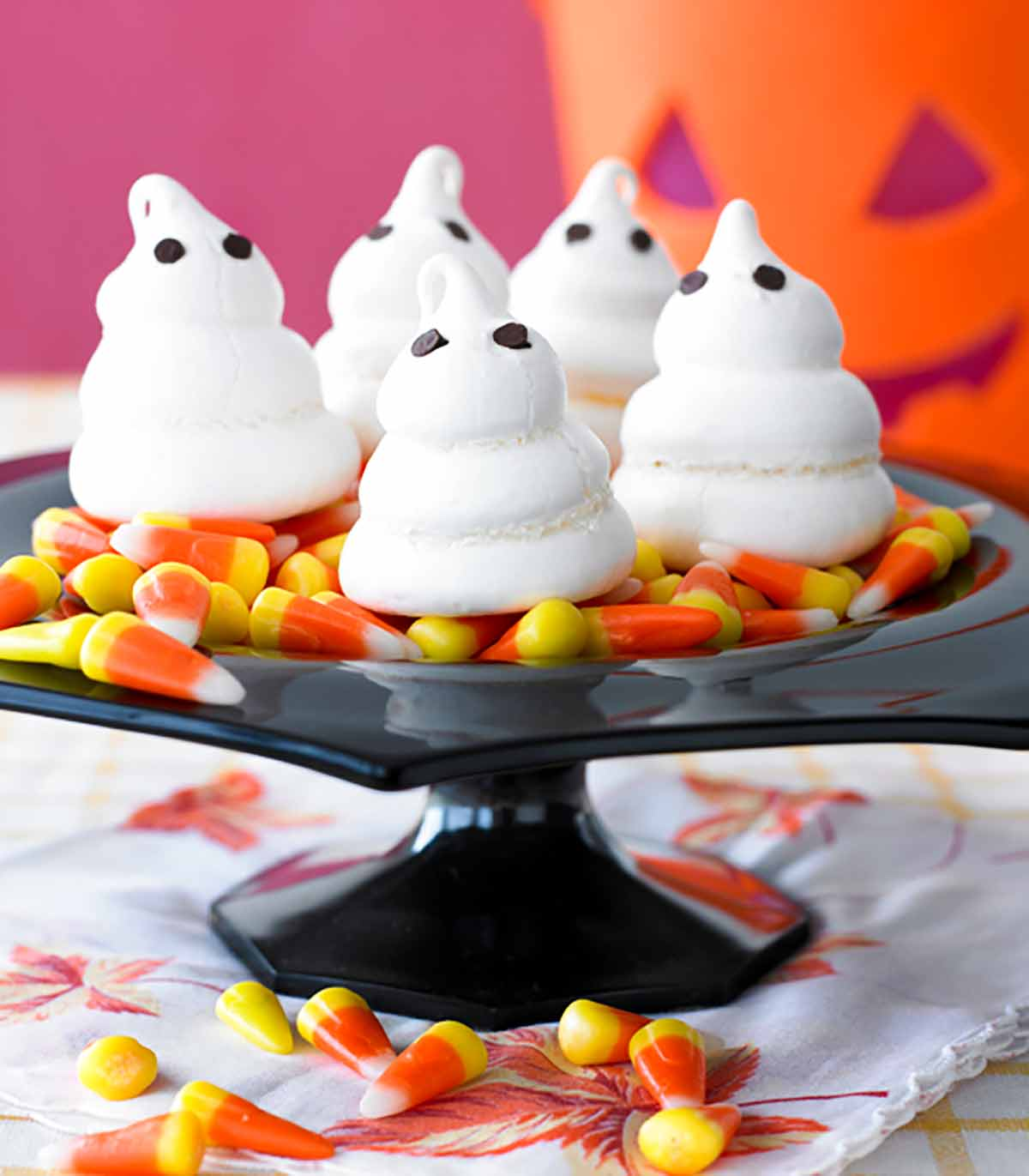 Four meringue ghosts on a bed of candy corn on a black cake stand.