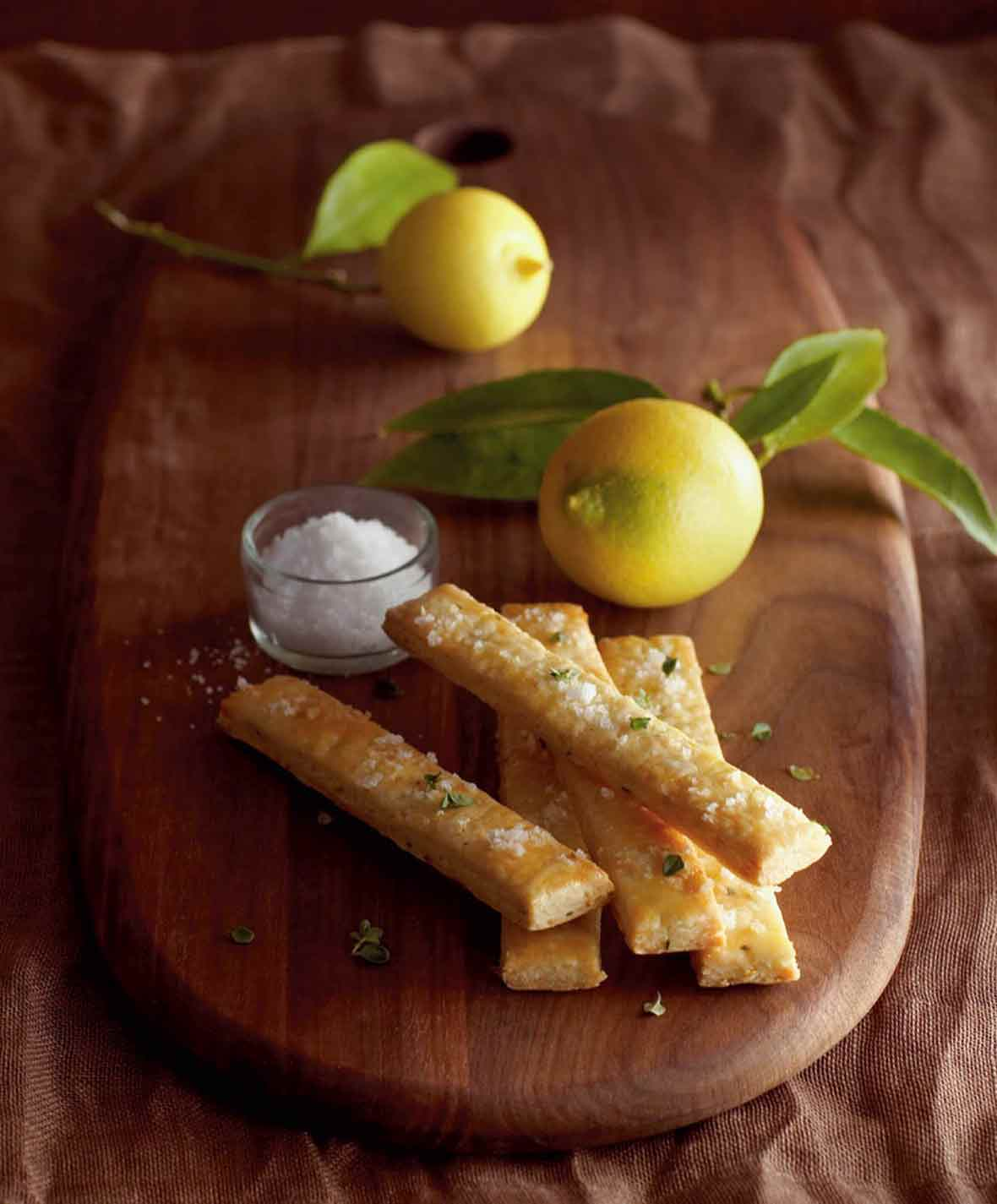 A stack of five lemon, thyme, and sea-salt shortbreads on a wooden board with a dish of sea salt and a lemon beside them.