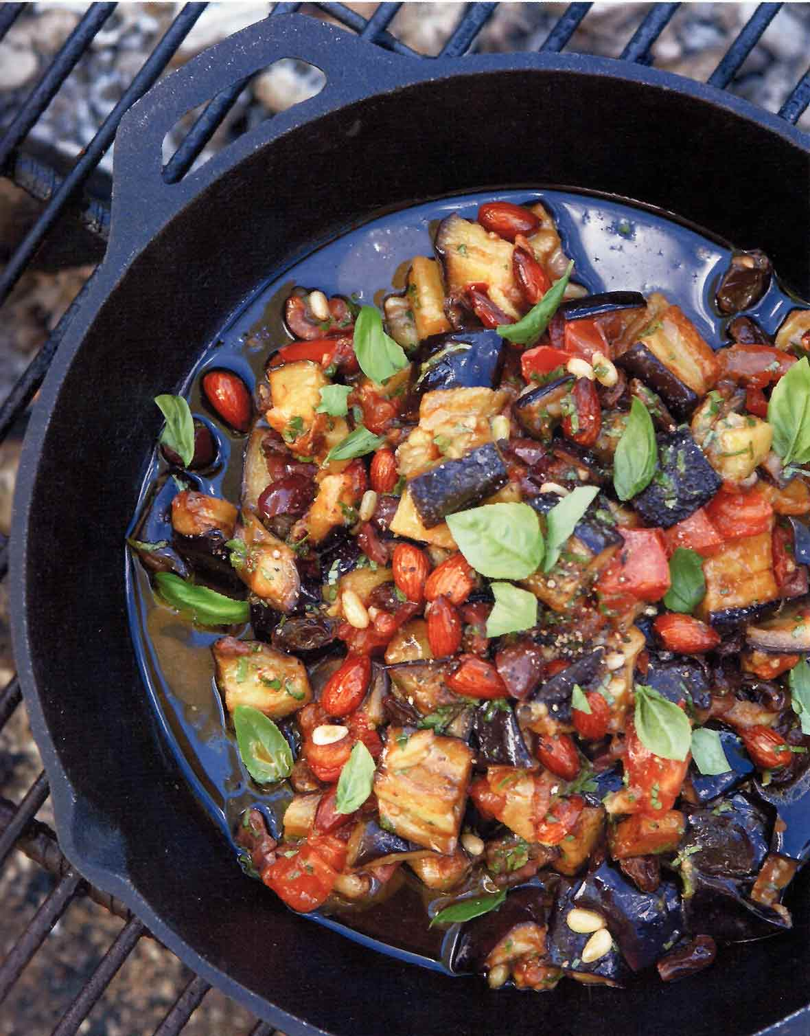 Skillet on a grill filled with eggplant caponata--chopped eggplant, onions, fennel, onions, almonds, basil