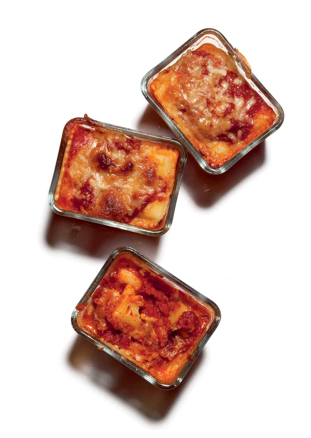 Three personal pan lasagnas in glass dishes.