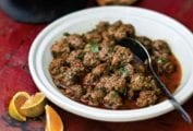 A white bowl filled with Moroccan meatballs with a spoon resting inside and some small orange wedges on the side.