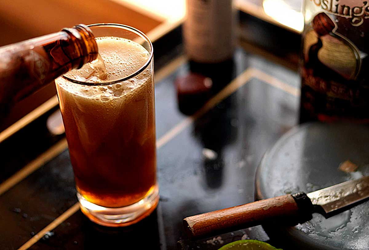 A tall glass filled with dark and stormy cocktail with ginger beer being poured in.