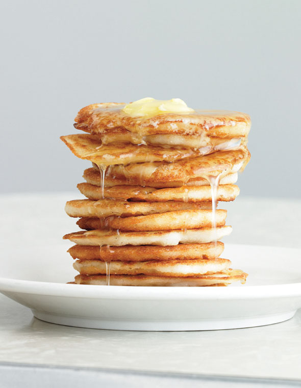 A stack of johnnycakes on a white plate topped syrup and butter.