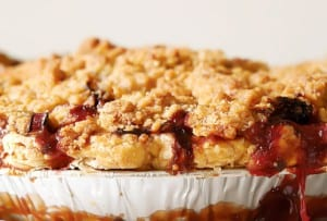 A side view of a strawberry rhubarb pie with ginger crumb topping.