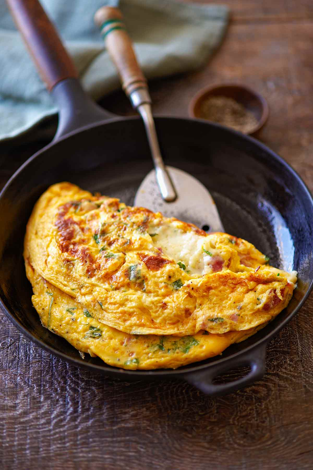 A cooked ham and cheese omelet in a small skillet with a spatula sliding underneath to flip it.