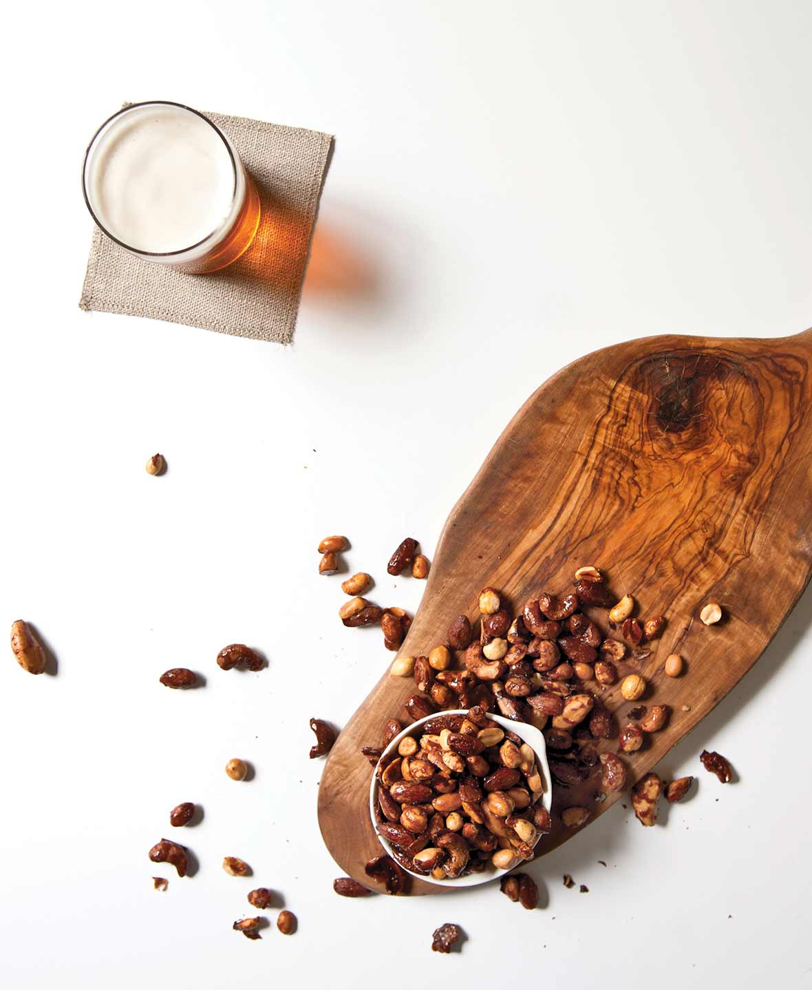 An overflowing bowl of beer nuts on a wooden board with a glass of beer on a napkin beside it.