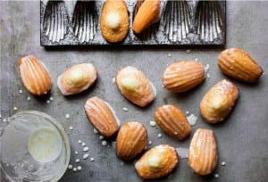 Several glazed lemon madeleines scattered next to a madeleine pan and a dish of glaze.