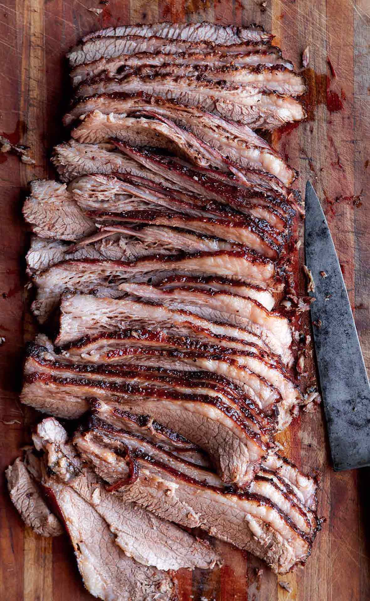 A sliced Texas brisket on a wooden board with a knife lying beside it.