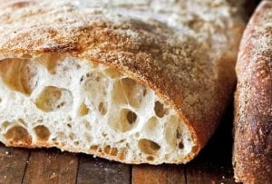 A loaf of ciabatta, sliced, and filled with large air holes