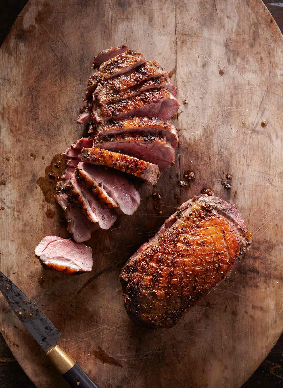 Two seared duck breasts, one sliced, the other whole on a wood cutting board
