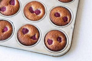 A muffin tin filled with raspberry-studded financiers.