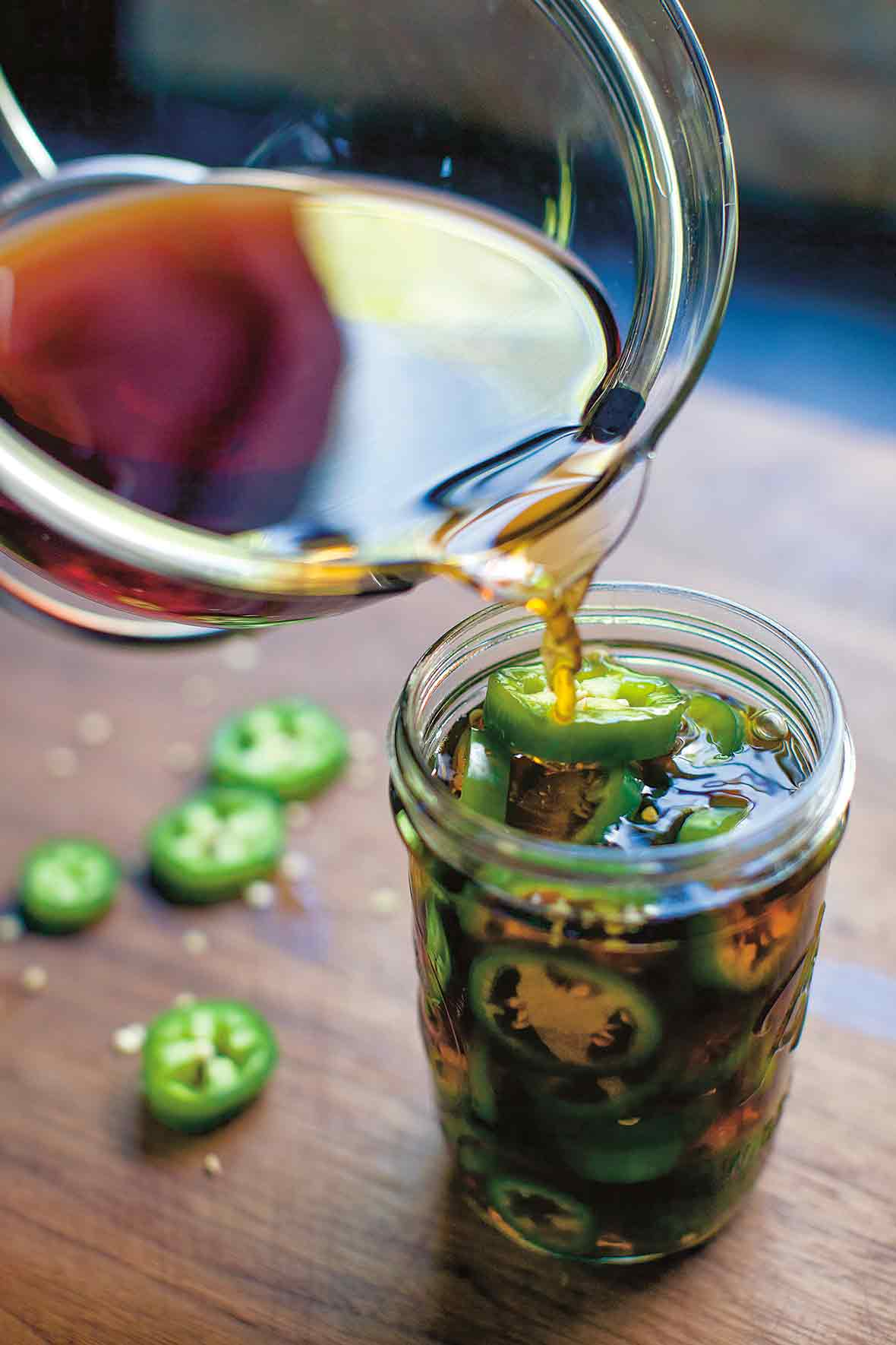 Pickling liquid being poured into a full jar of pickled jalapeno peppers.