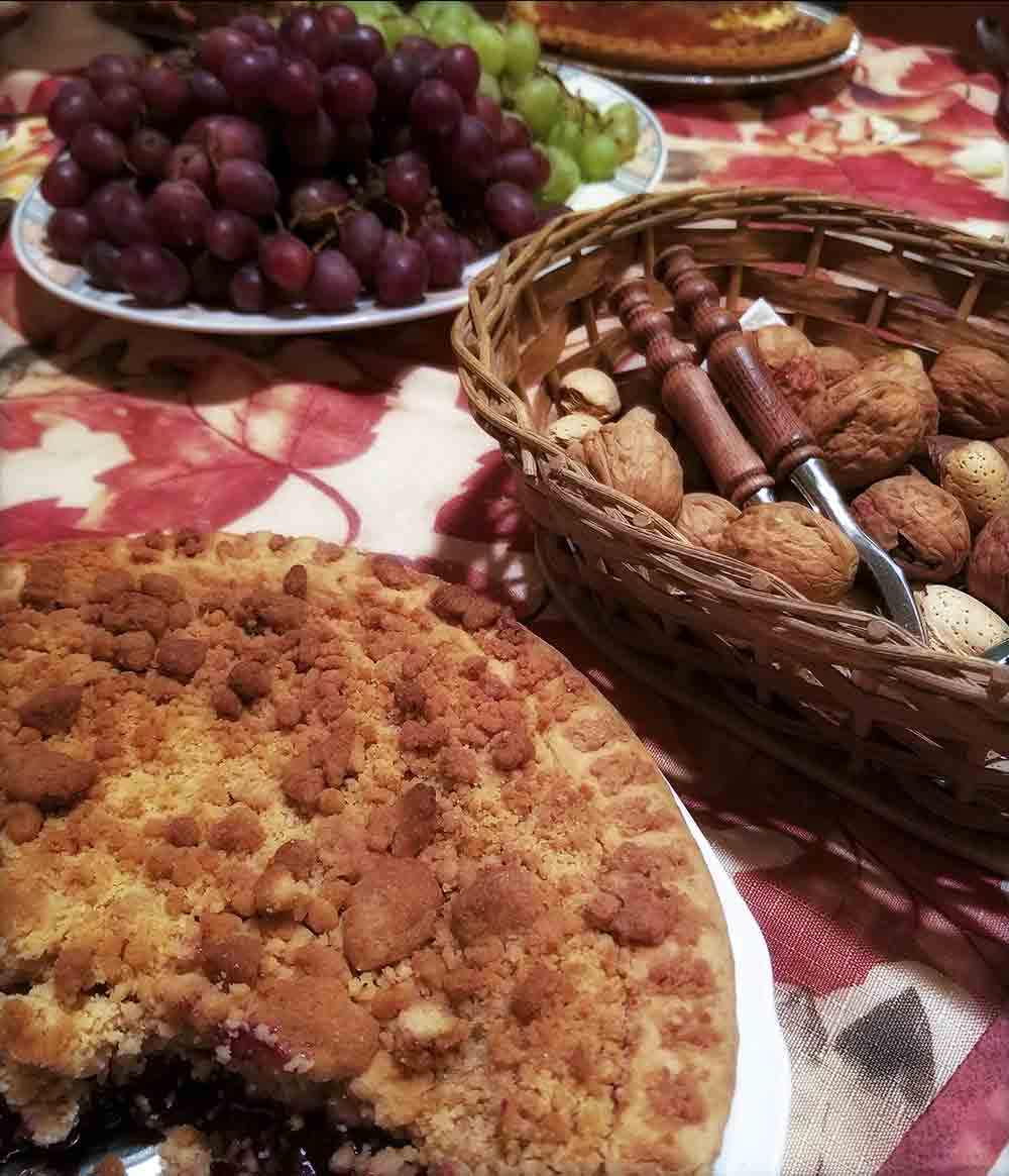 Table with a basket of  nuts, a cake, and grapes