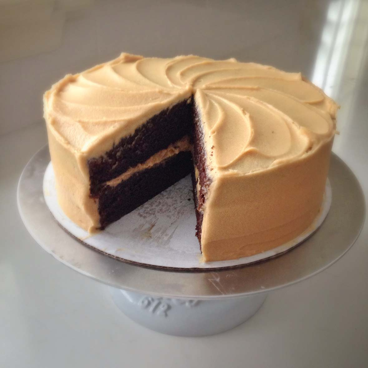 A sour cream mocha cake on a cake stand with one slice missing.