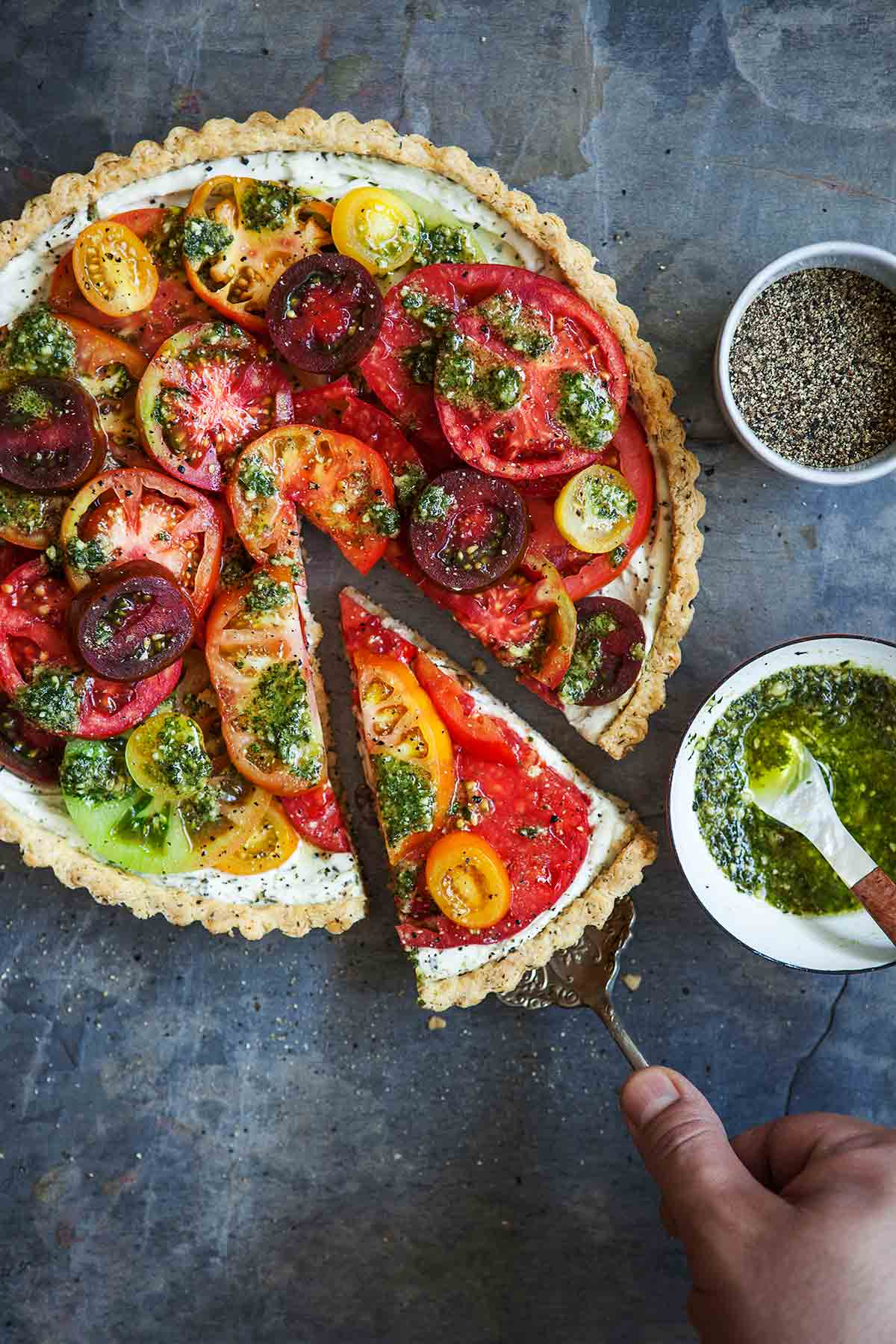 A person removing a slice of fresh tomato tart with a lifter and a bowl of pesto and black pepper on the side.