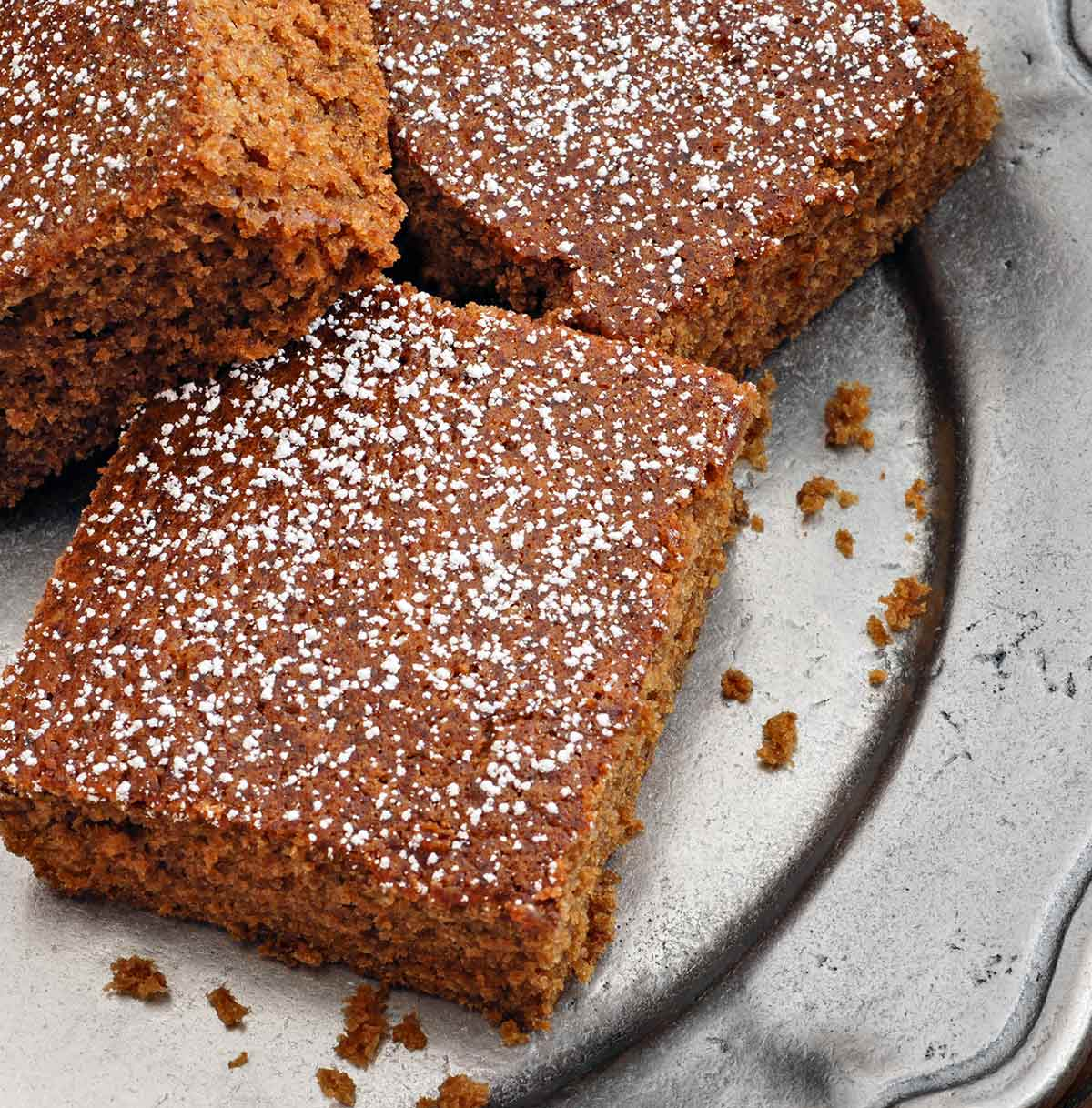 Squares of best homemade gingerbread cake dusted with confectioners' sugar on a silver platter.