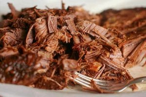 A plate of shredded Coca-Cola brisket with a fork resting in the meat.