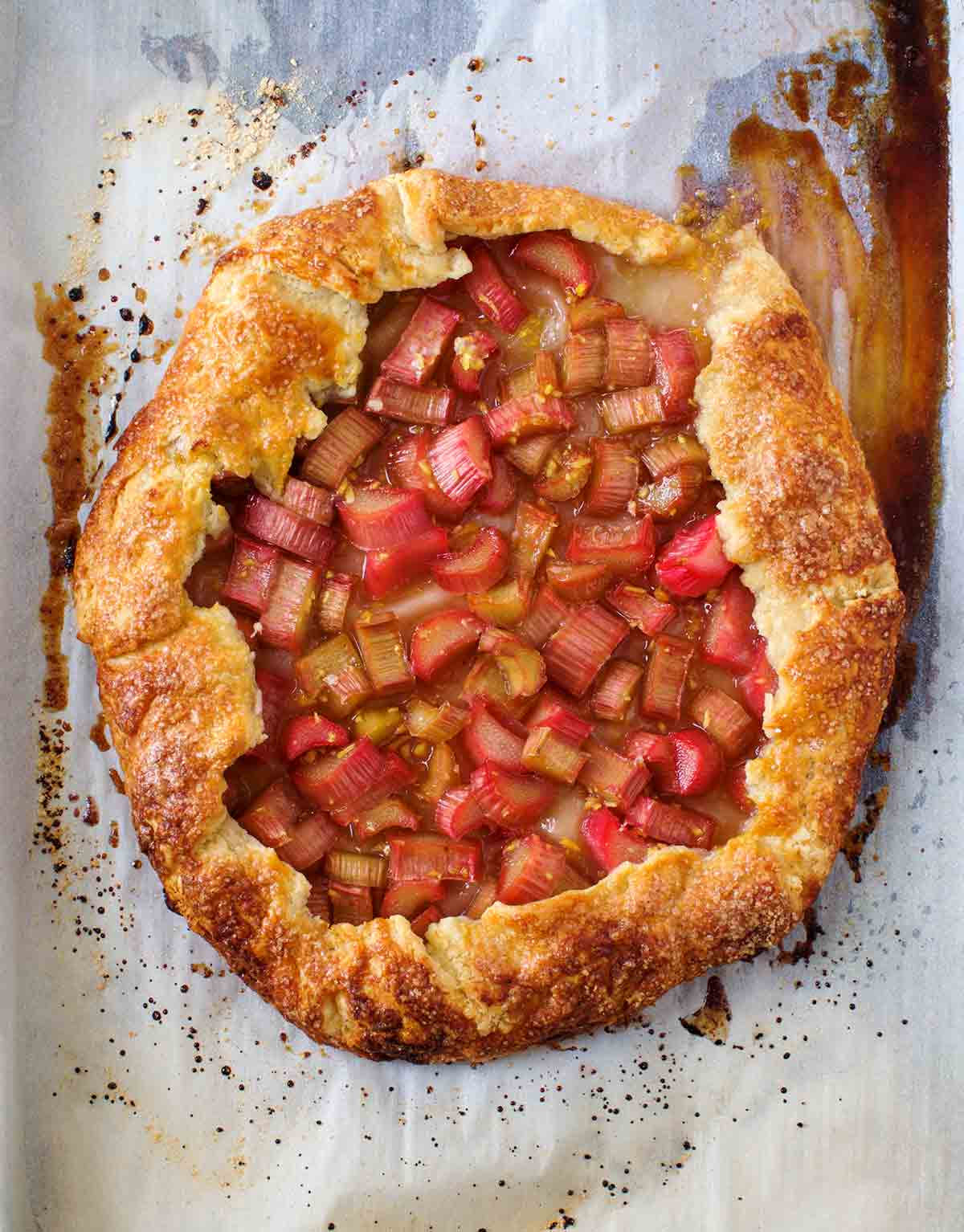 A whole baked rhubarb-ginger crostata on a piece of parchment paper.