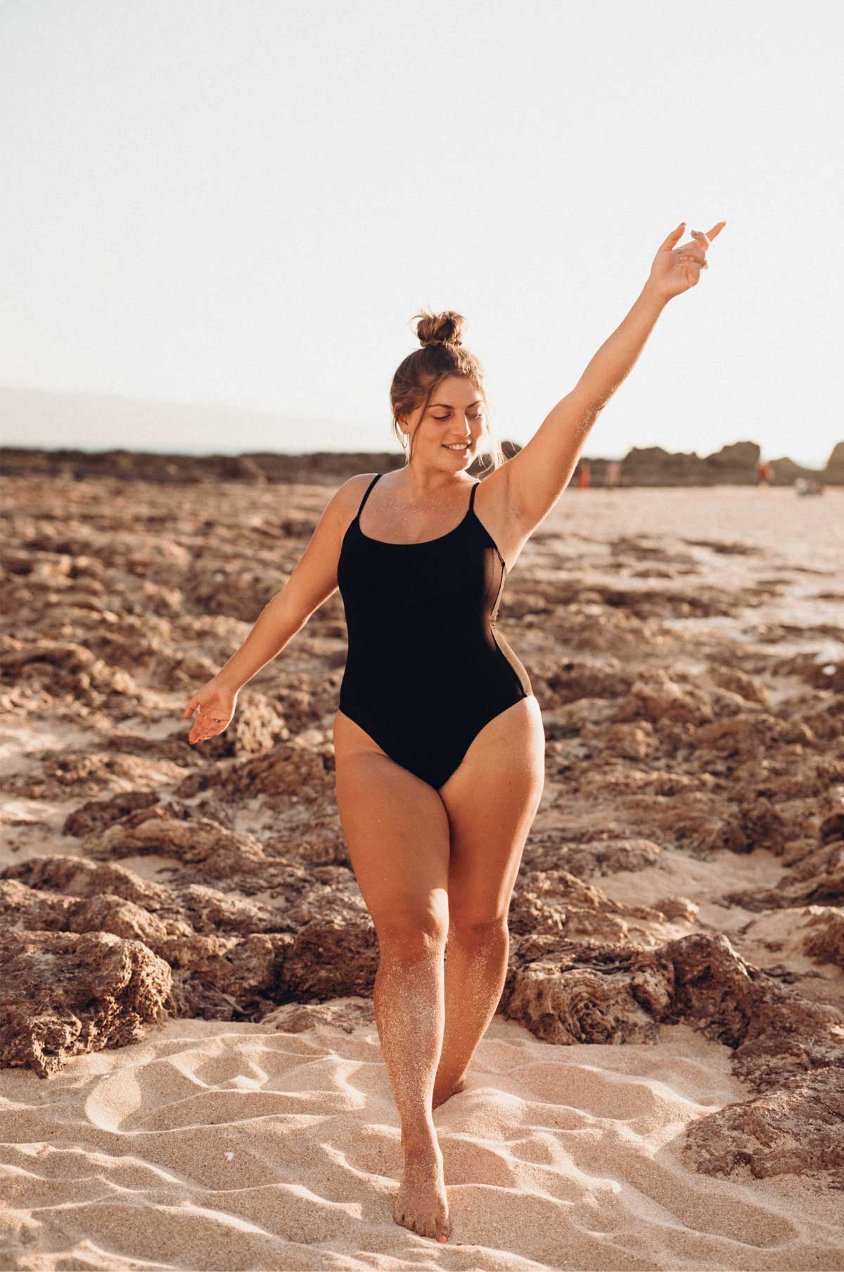 A plus size woman in a black bathing suit on the beach for the post 'how to be fat'.