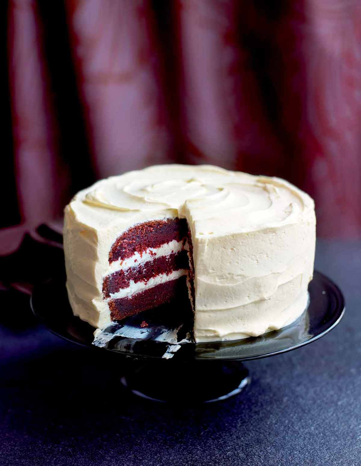 A red velvet cake with cream cheese frosting on a cake stand