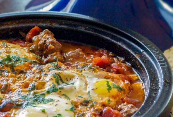 Kefta Mkaouara, or Moroccan meatball-tomato-and-egg tagine, in a blue pot sprinkled with parsley