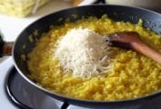 Skillet on the stove filled with risotto alla Milanese, a pile of cheese, and a wooden spoon