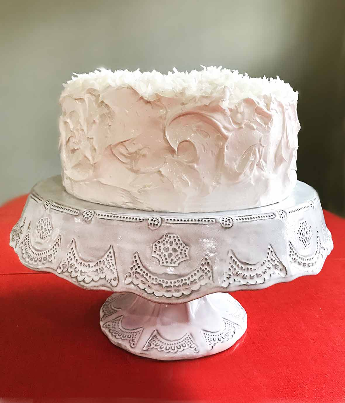 Coconut layer cake with white meringue frosting topped with shredded coconut on a white cake stand on a red table