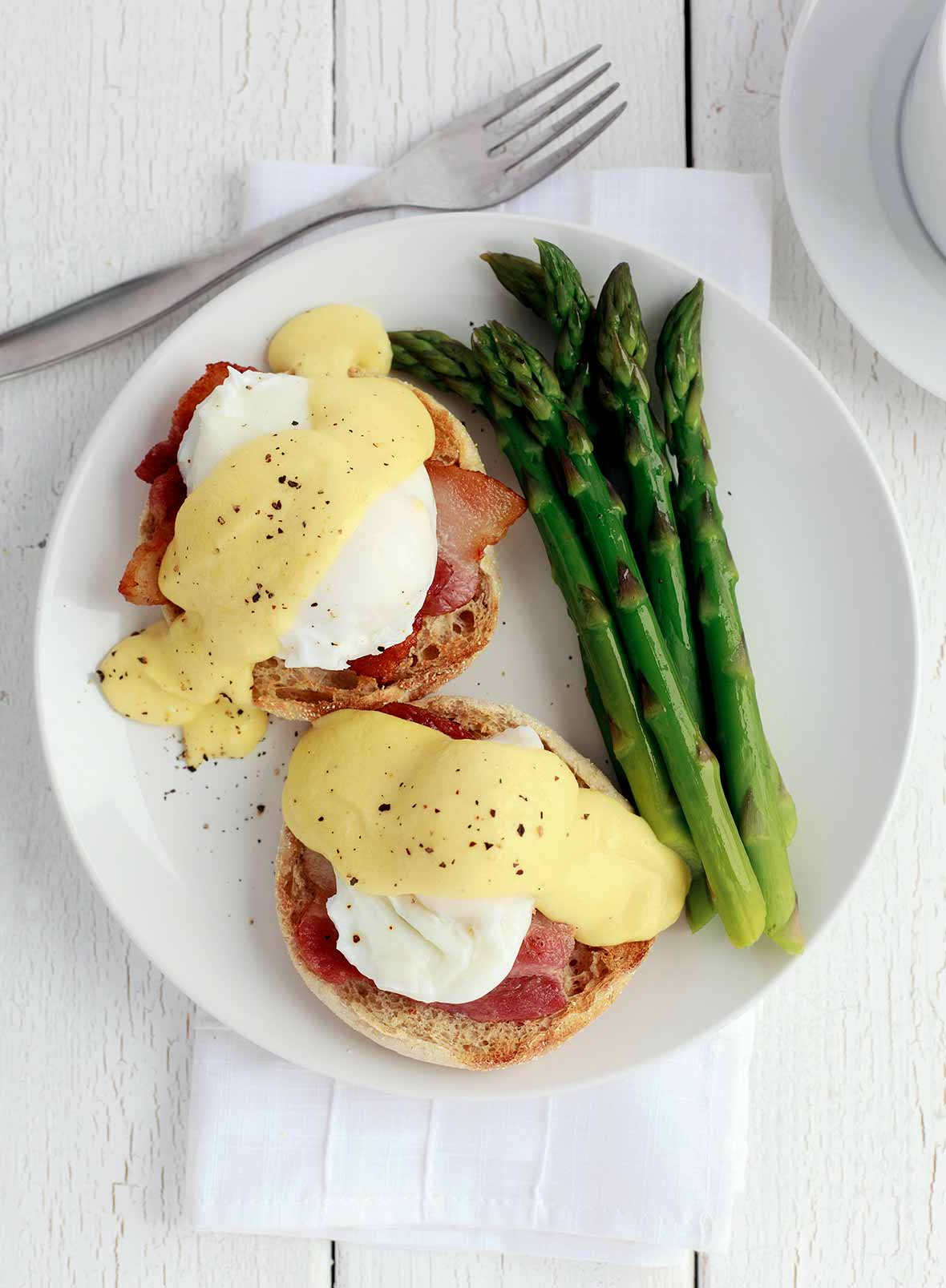 Two Julia Child's eggs Benedict on a white plate with a side of asparagus.