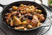 Black skillet with a French chicken fricassee, called chicken grand-mere, with onions, mushrooms, potatoes