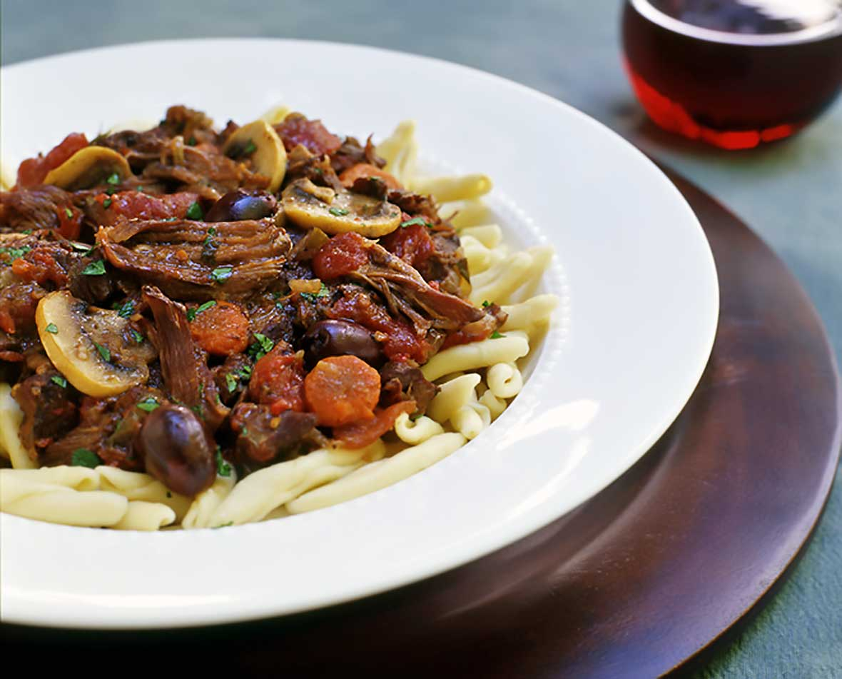 Bowl of french beef stew with sliced carrots over pasta sitting on a wooden tray