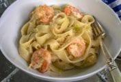 A bowl filled with shrimp and leek Pasta--large shrimp, wide noodles, chopped leeks, and cheese