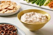A yellow bowl filled with California dip, a plate of pretzels, a bowl of pita chips, and a platter of raw vegetables.