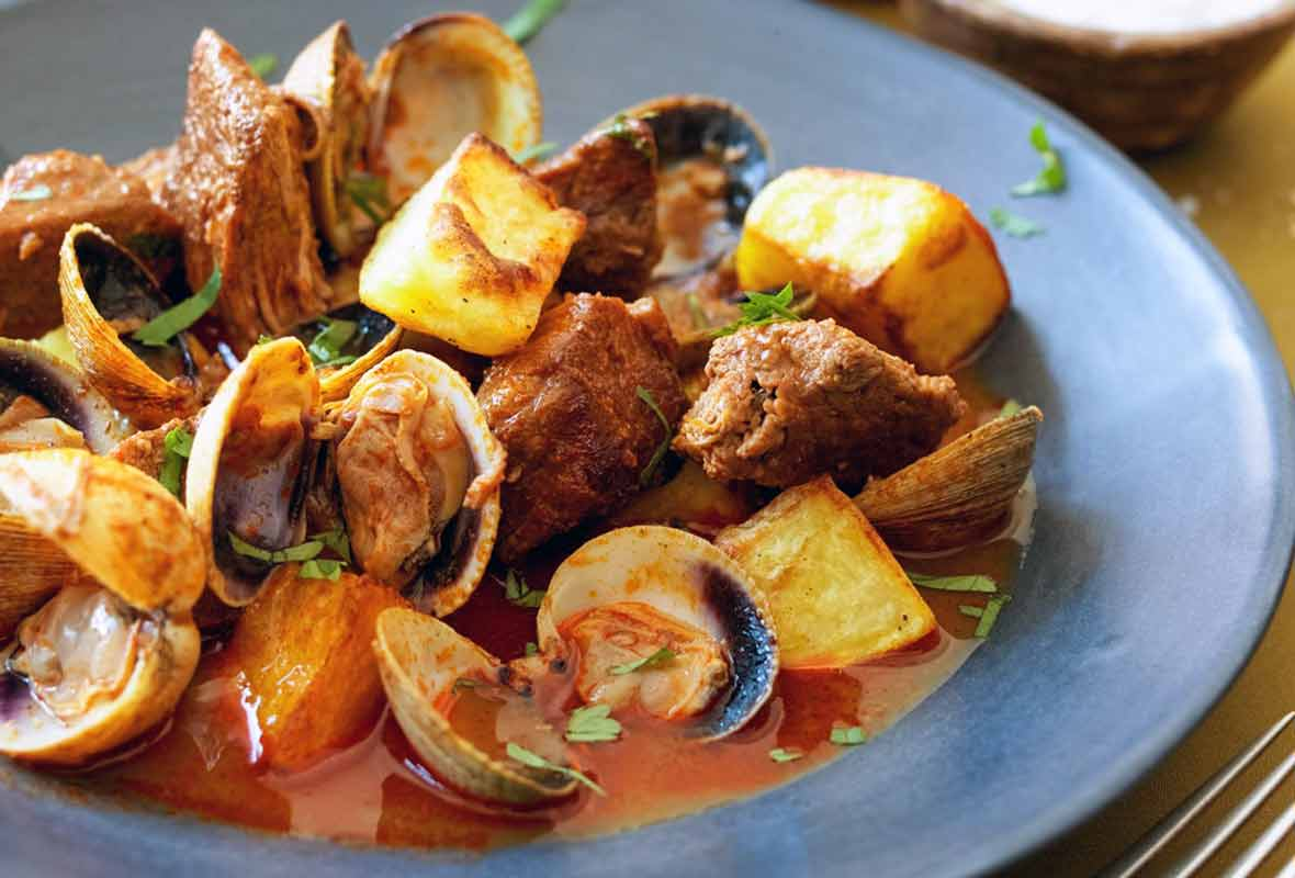 A blue bowl filled with Portuguese pork with clams and fried potato cubes.