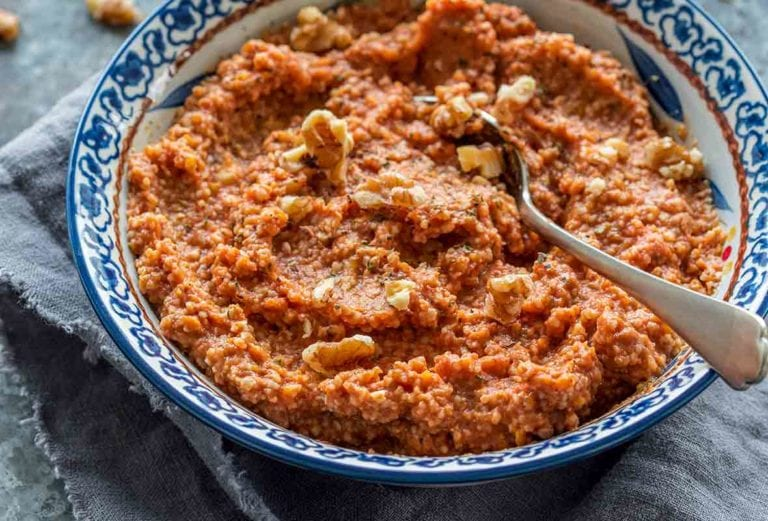 Blue and white bowl filled with Muhammara, or red pepper walnut spread with a spoon in it