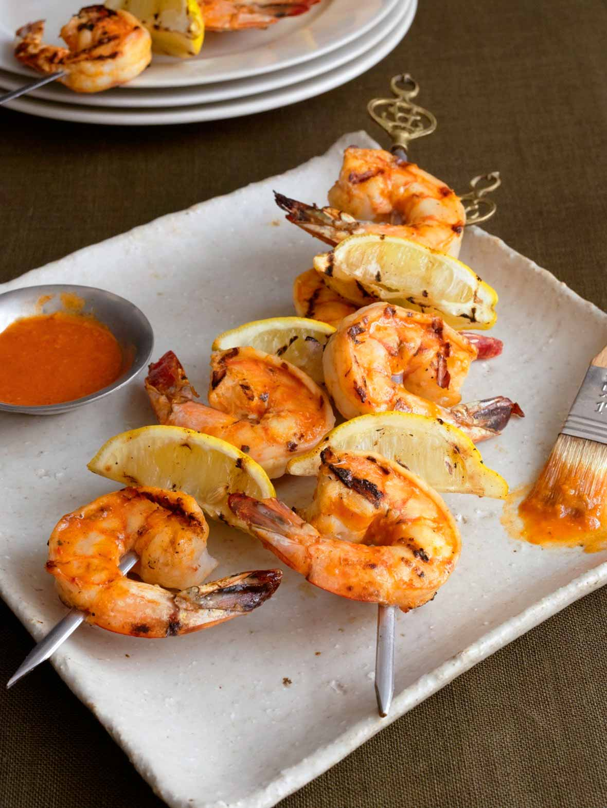 A white square platter with two skewers of grilled Portuguese shrimp with piri piri sauce and lemon wedges, a small dish of piri piri sauce, and a basting brush.