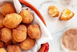 A red pot filled with sonhos dusted with cinnamon sugar and one cut Portuguese doughnut resting beside the bowl