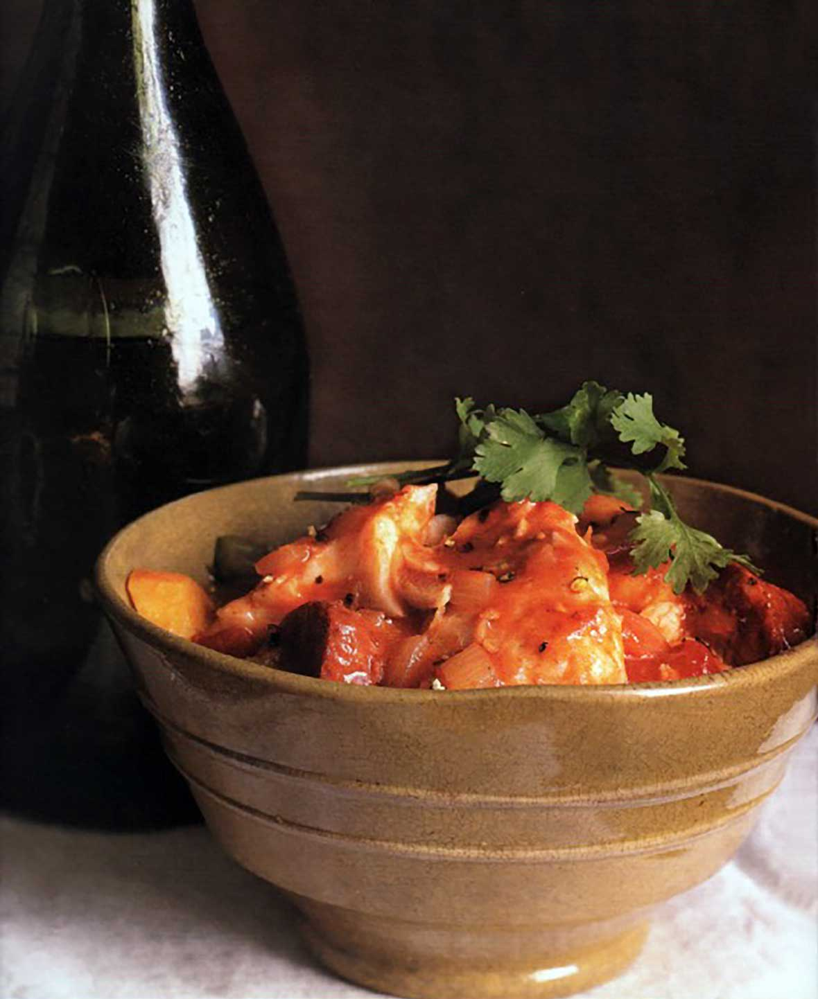 A brown ceramic bowl filled with Portuguese fish chowder, made with fish, potatoes, chouriço, tomatoes, and cilantro.