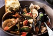Bowl of Portuguese fisherman's stew, which includes, clams, mussels, cod, tomatoes, and herbs--a slice of bread