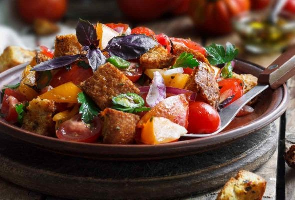 Wood bowl of panzanella from Ina Garten with bread chunks, tomatoes, peppers, cucumbers, basil, and parsley