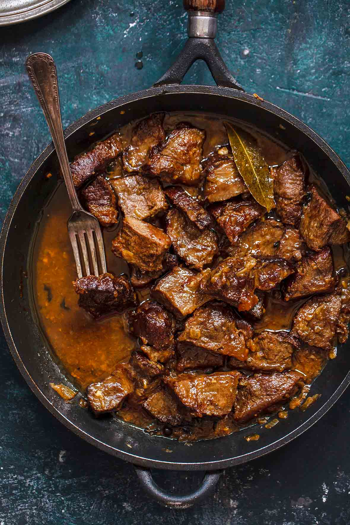 A cast iron skillet with cacoila--or chucks of Portuguese stewed beef, bay leaf, and a fork