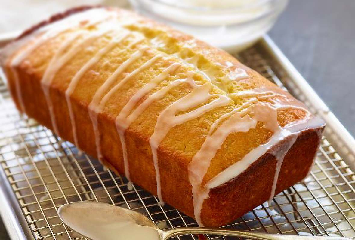 Ina Garten's lemon cake, a pound cake, on a rack, drizzled with a lemon glaze, a spoon nearby