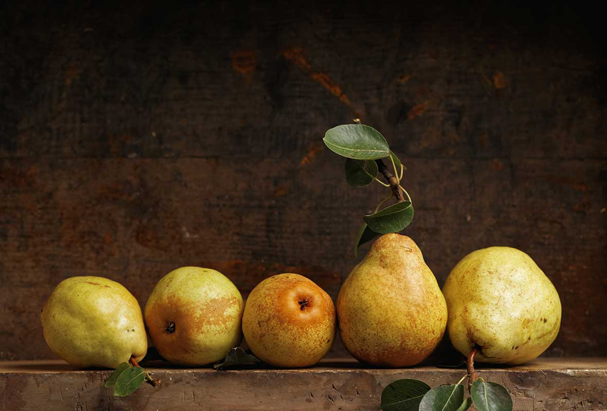 Row of five pears in front of a black background