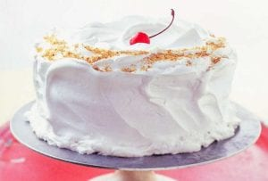 A Lady Baltimore cake covered with billowy white frosting on cake stand