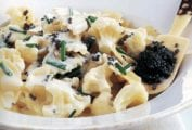 A bowl of bowtie pasta with caviar, in a cream sauce topped with chives