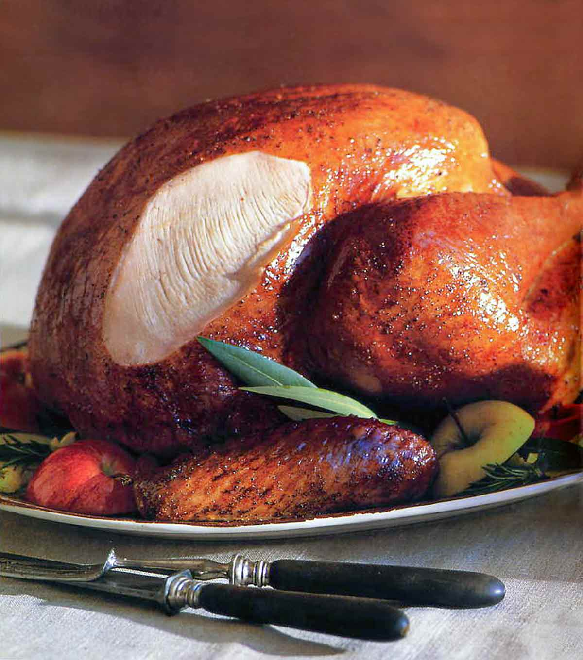 A classic roast turkey on a platter with pieces of apple and rosemary sprigs tucked around it.