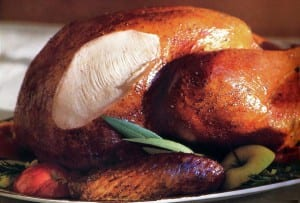 A classic roast turkey with giblet gravy on a platter with apple pieces and bay leaves.