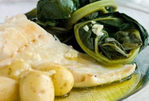 A white plate of bacalhau consoada or Portuguese Christmas Eve cod, with salt cod, small potatoes, and blanched kale
