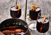 Three glasses of glogg (mulled wine) with orange slices and cinnamon sticks
